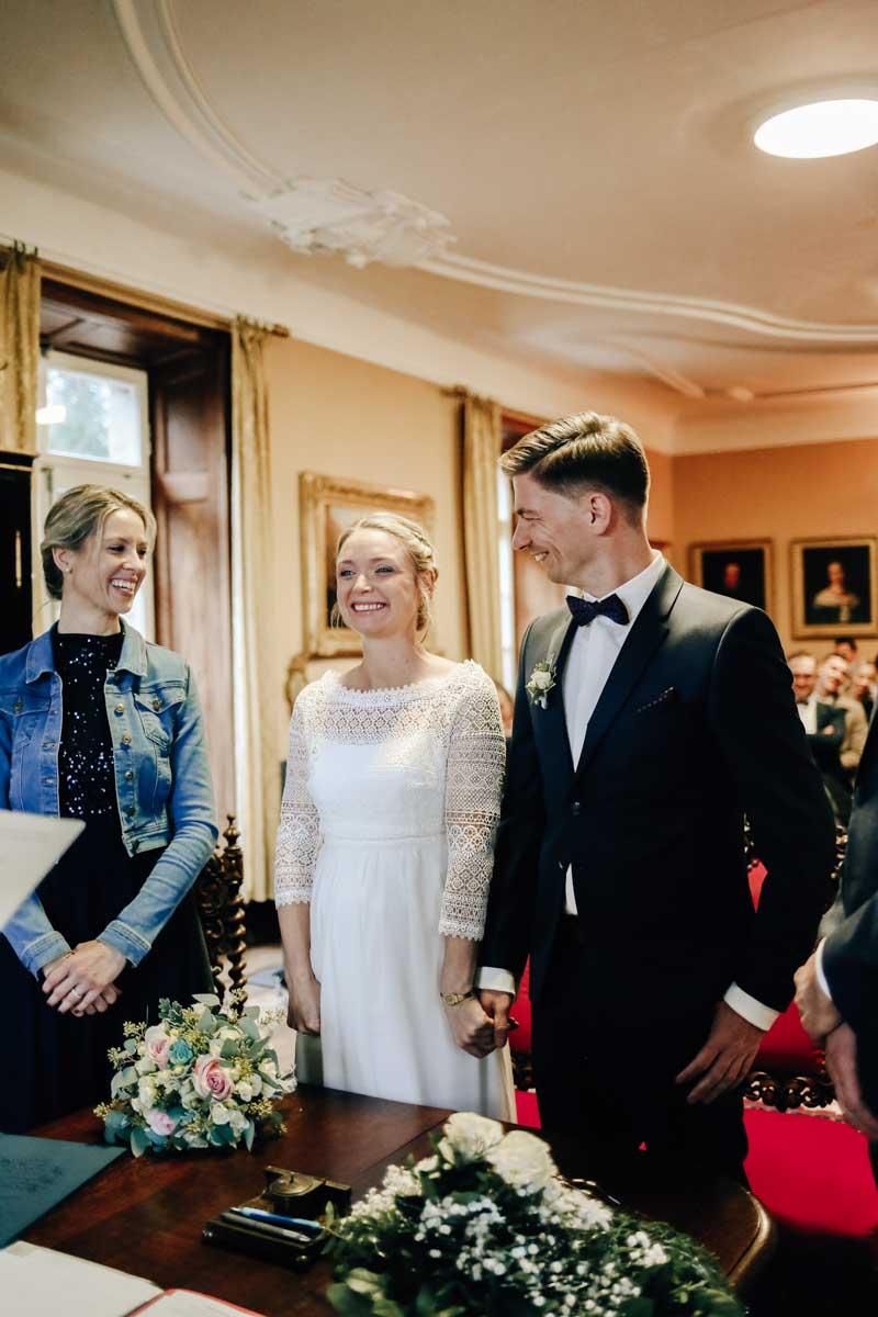 Lachendes Brautpaar bei der Trauung