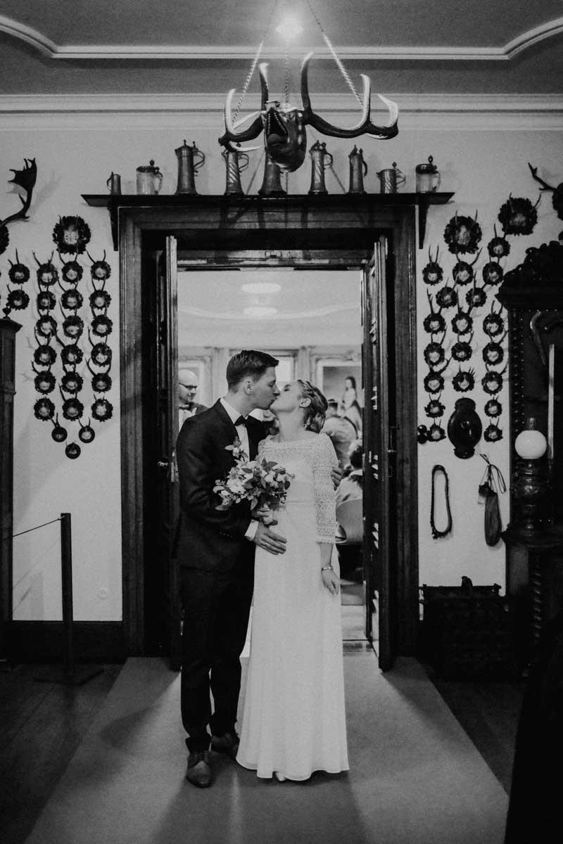 Brautpaar steht im Flur und küsst sich
