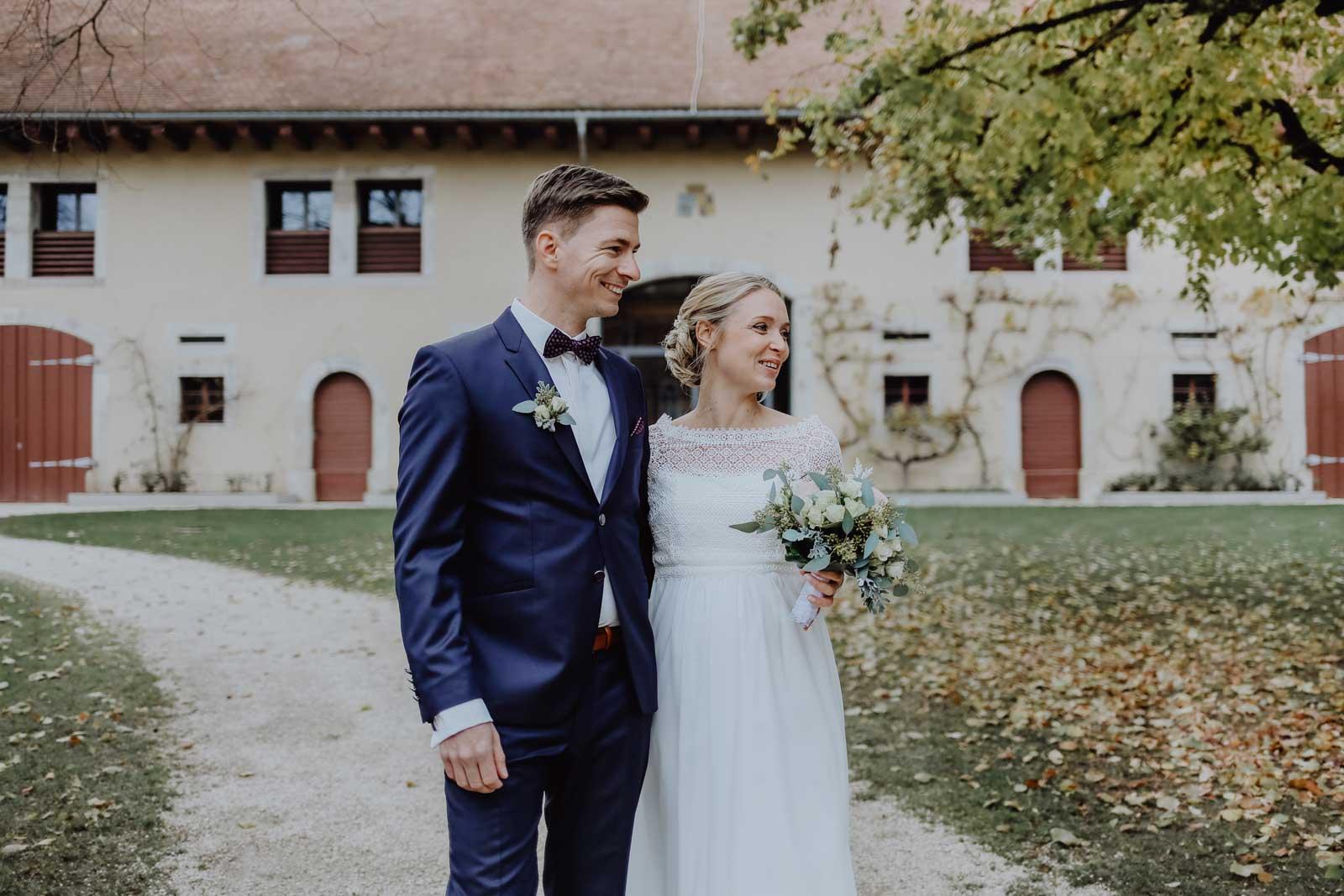 Bräutigam umarmt Braut mit Brautstrauß