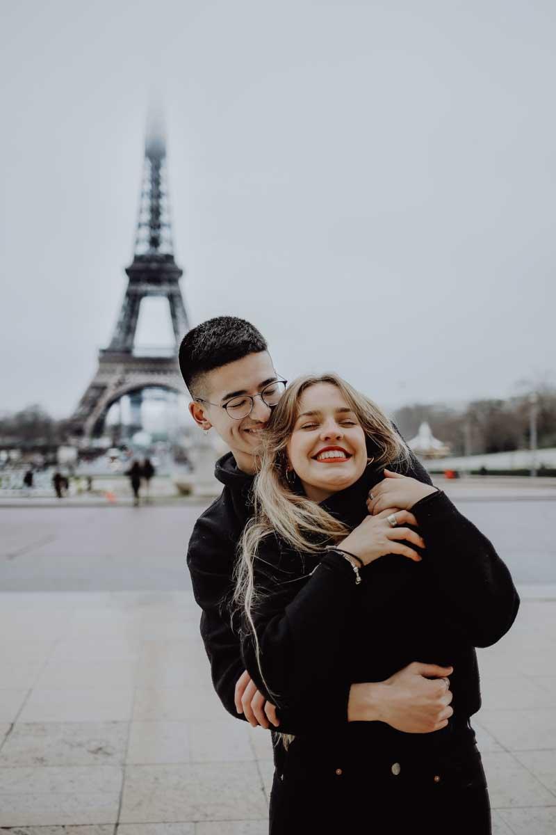 Mann umarmt Frau vor dem Eiffelturm