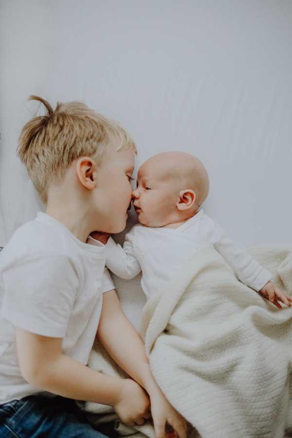 Junge mit Baby am Kuscheln