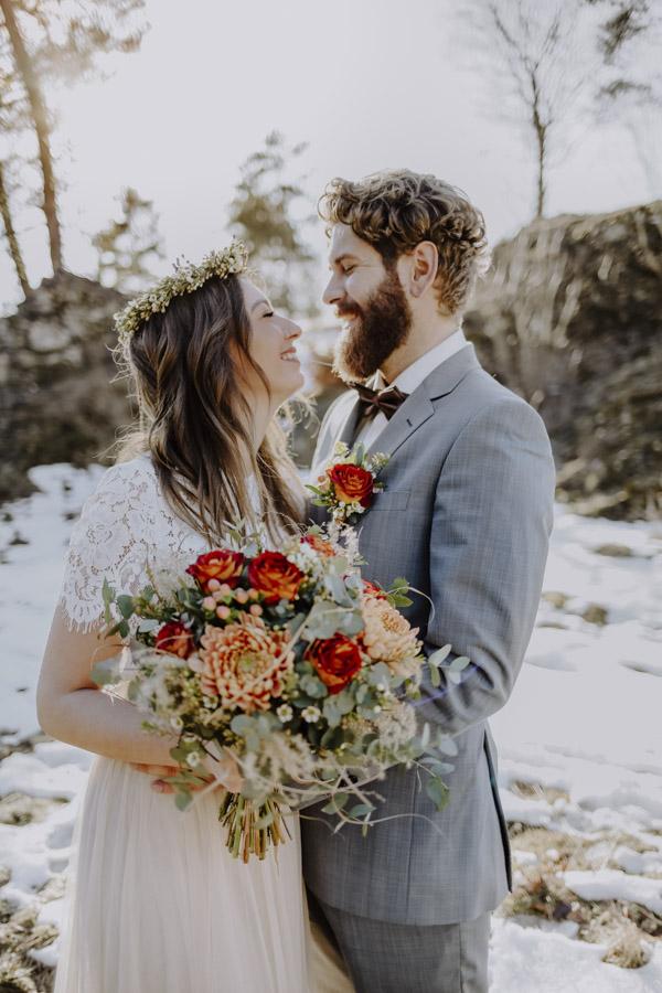 Braut und Bräutigam mit Brautstrauß vor Felsen