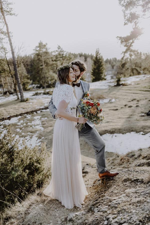 Bräutigam und Braut stehen auf Berg mit Schnee
