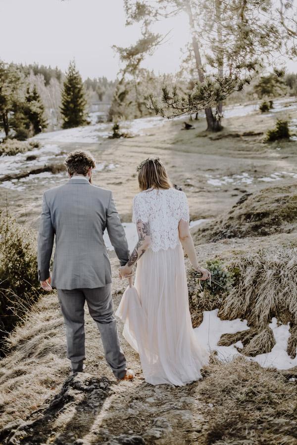 Bräutigam und Braut laufen Berg hinunter