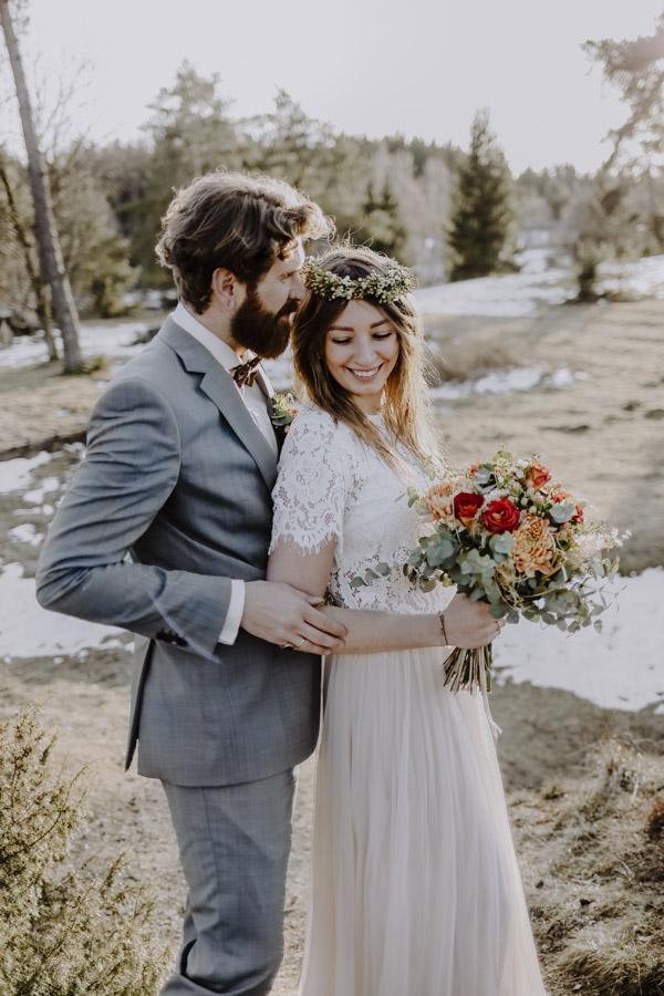Braut schmiegt sich an Bräutigam auf Wiese