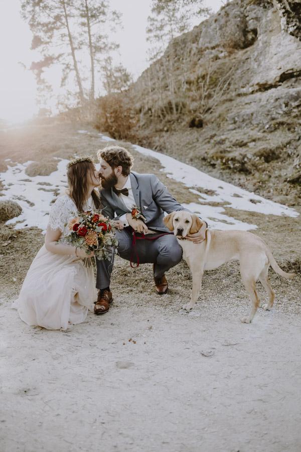 Küssendes Brautpaar mit Hund vor Baum