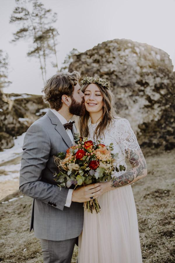 Bräutigam küsst Braut mit Brautstrauß