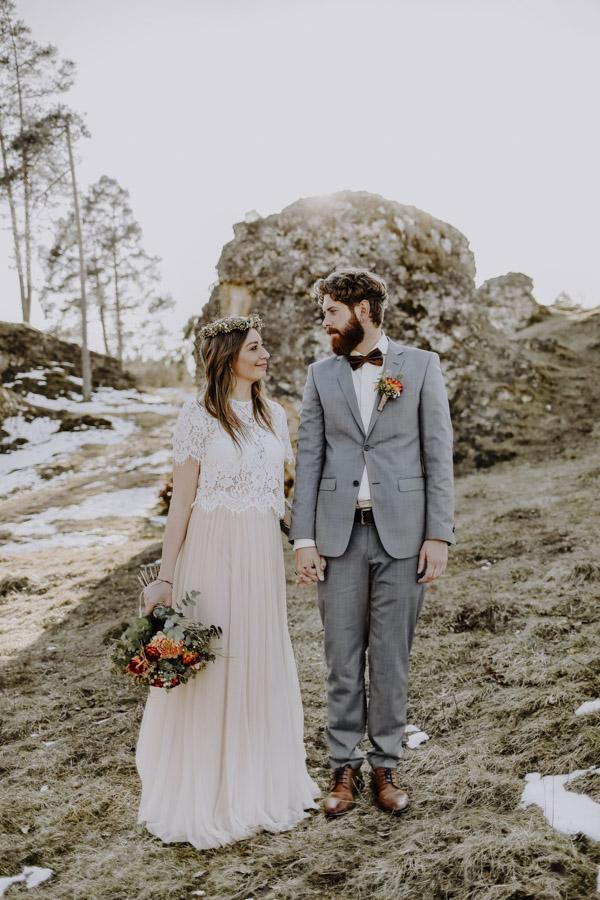 Brautpaar steht vor einem Fels auf Wiese