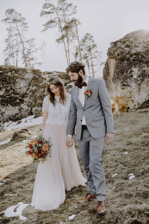 Brautpaar geht Hand in Hand den Berg hinunter