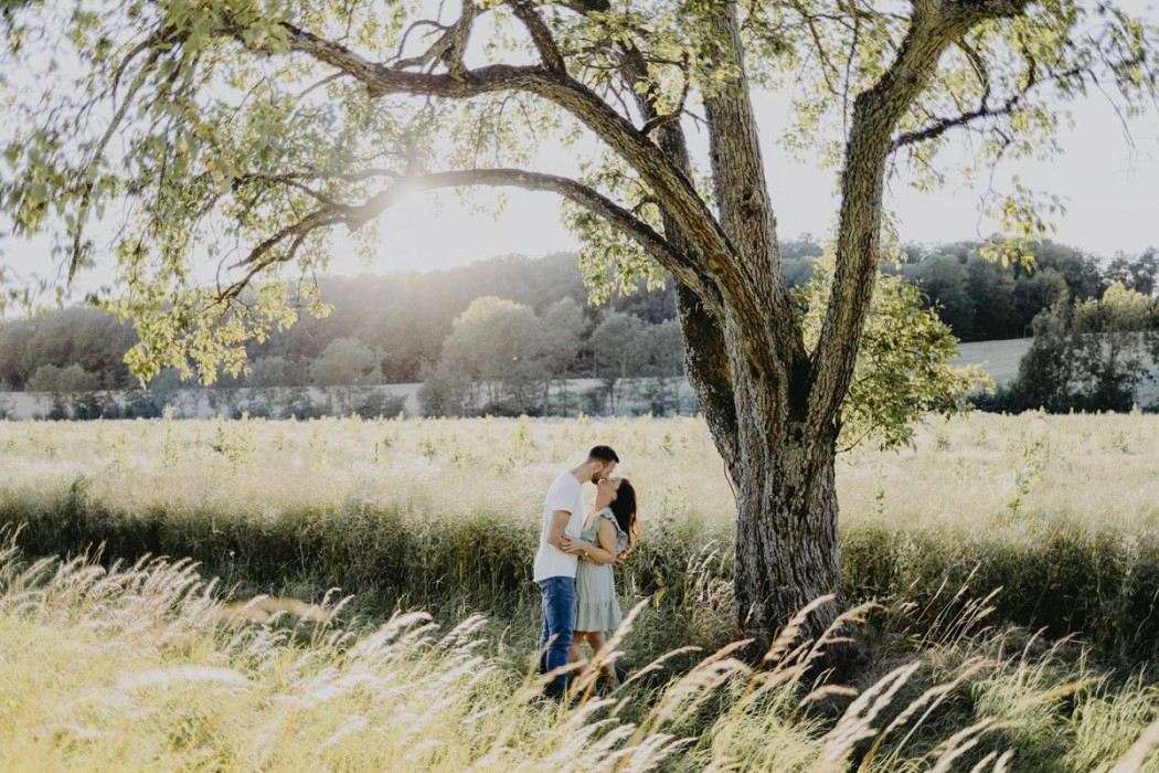 Paar in Wiese neben Baum