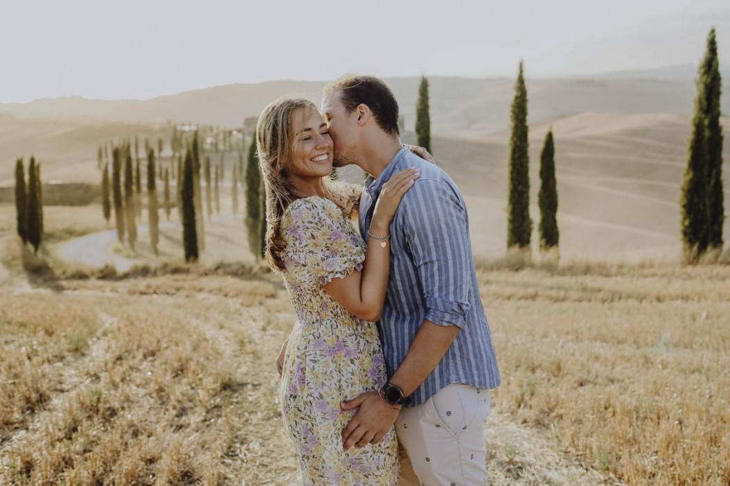Mann küsst Frau auf Feld