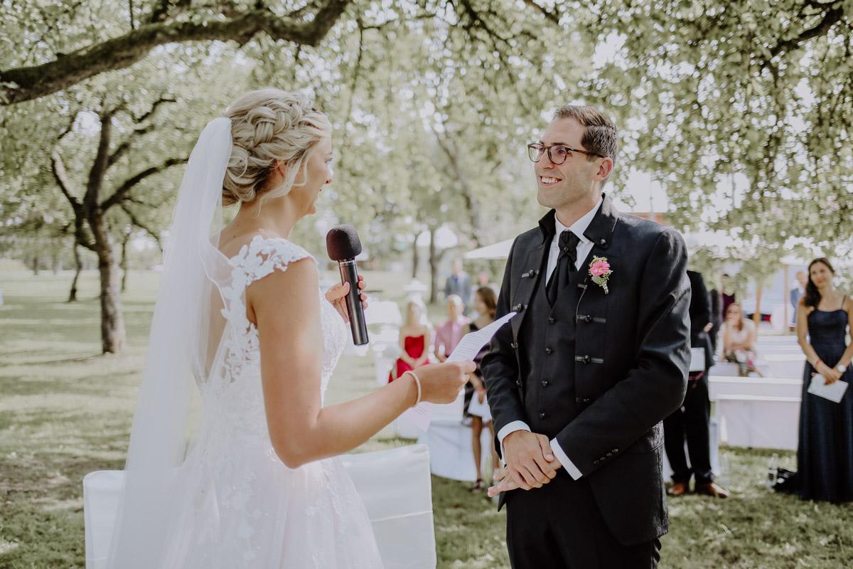 Frau steht Mann gegenüber mit Mikrofon in der Hand