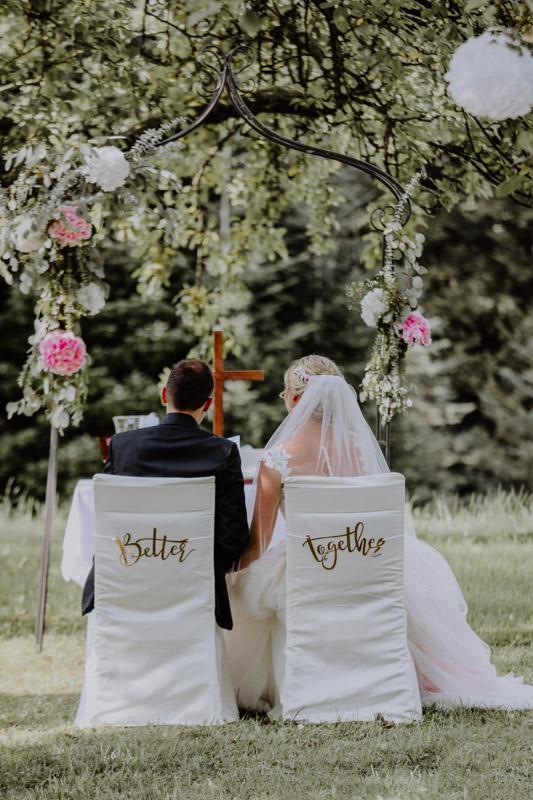 Brautpaar sitzt auf Stühlen