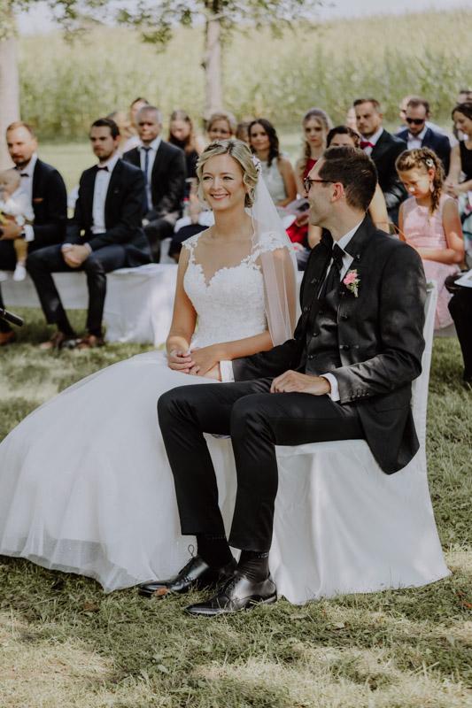 Brautpaar und Gäste auf Wiese